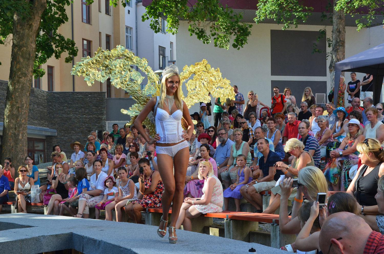 Modelka procházející po přehlídkovém molu na letní scéně Eurocentra v Jablonci nad Nisou ve spodním prádle a luxusní bižuterii v podobě korunky, náhrdelníku a andělských křídel na veletrhu skla a bižuterie Křehká krása