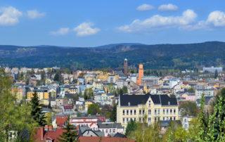 Celkový pohled n apanorama Jablonce nad Nisou - věž radnice, kostela a Jizerské hory v pozadí