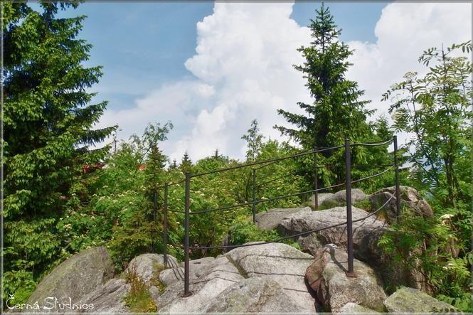 Skalní vyhlídka obklopená stromy u rozhledny Černá Studnice - Jablonecko