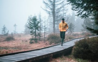 Muž běžící po přírodním dřevěném chodníčku v mlze v Jizerských horách. Sportovní duch.