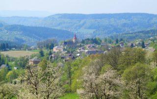 Celkový pohled na malebnou vesnici na Jablonecku – Bzí. V pozadí Krkonoše.