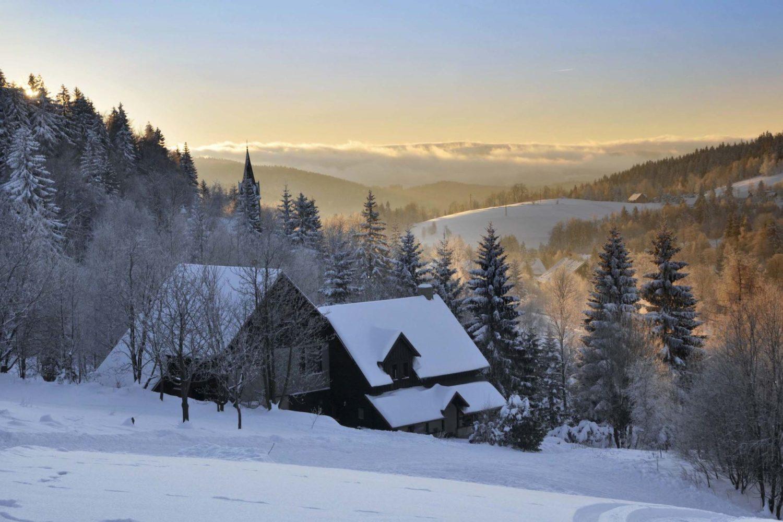 Zasněžená horská chalupa v Bedřichově a zapadající slunce v Jizerských horách