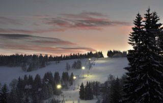 Sjezdovka v Bedřichově v Jizerských horách osvětlená pro večerní lyžování.