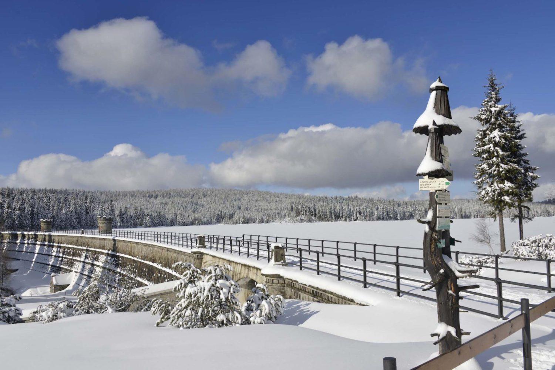 Zasněžená hráz přehrady na Černé Nise v Jizerských horách, vpopředí turistický rozcestník