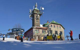 Restaurace a rozhledna Tanvaldský Špičák (Skiaréna Jizerky) v zimě. Lanovka a lyžaři vpopředí.