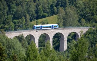 Vlak projíždějící na vysokém mostě krajinou v Libereckém kraji