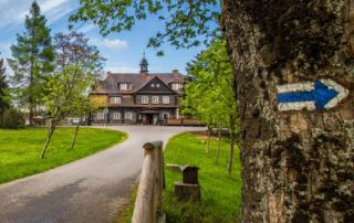 Šámalova chata na Nové Louce v Jizerských horách, vpopředí modrá turistická značka - oblíbená zastávka turistů, cyklistů i lyžařů, trasa Jizerské 50