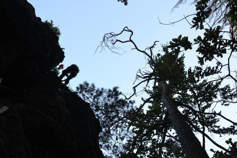 Pohled zdola na lezce a skálu - Via ferrata Vodní brána v oblasti přírodní rezervace Údolí Jizery