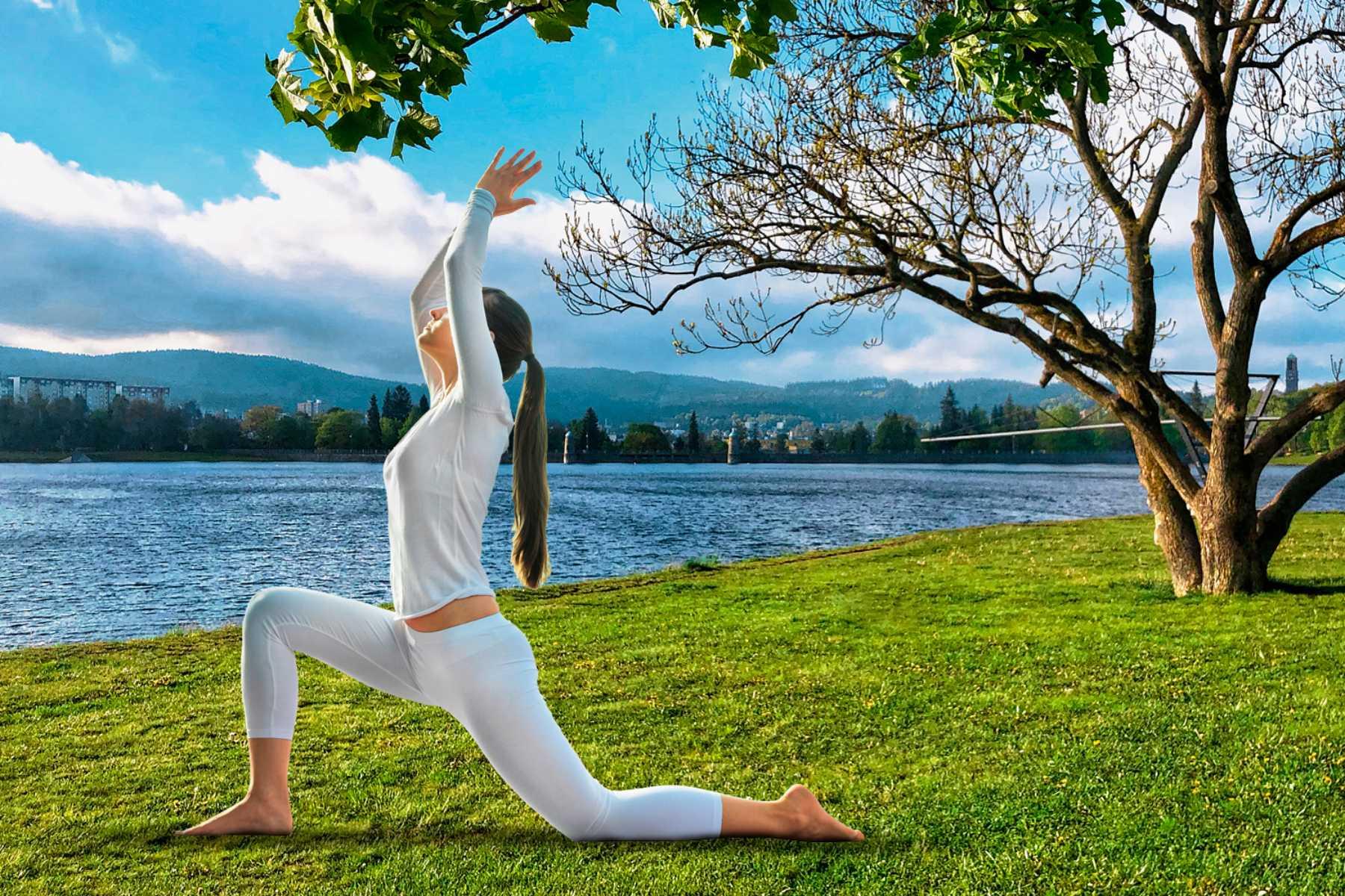 Žena v bílém cvičící jógu na trávě u vody - přehrada Mšeno Jablonec nad Nisou