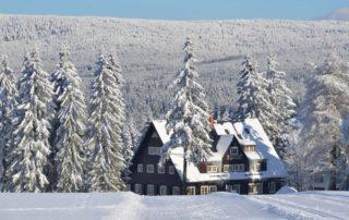Zasněžená Prezidentská chata uprostřed lesů v Jizerských horách