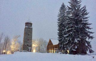 Kamenná rozhledna Bramberk a nově postavená chata s restaurací vedle ní - v zimě, pod sněhem vpodvečer. Jablonec nad Nisou. Jizerské hory