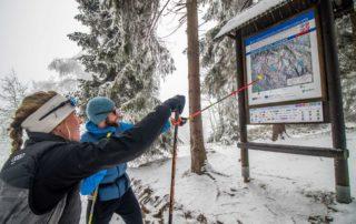 Dva běžkaři ukazující na mapu Jizerské magistrály - Jizerské hory