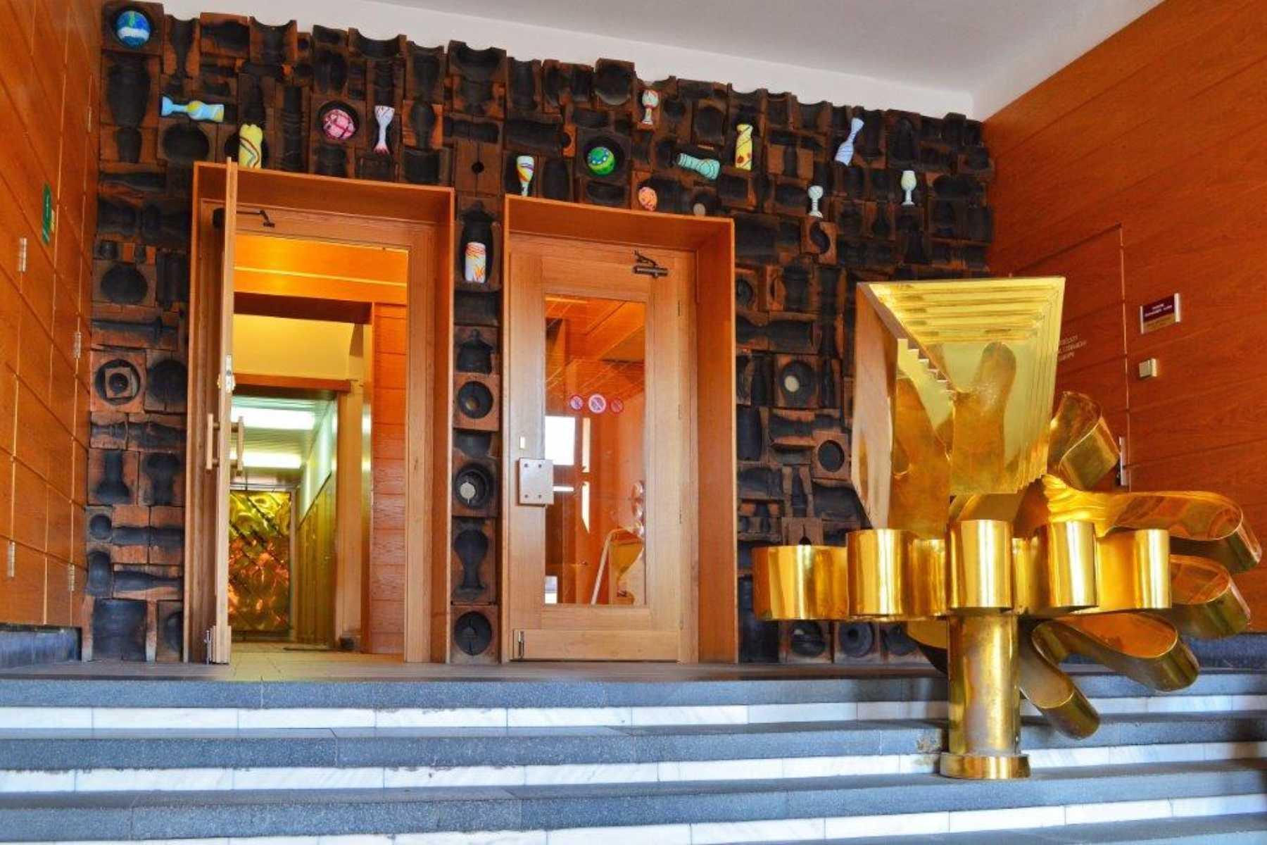 Plastika ruky s knihou ve zlaté barvě ve vstupní hale Městské knihovny v Jablonci nad Nisou