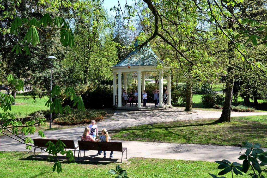 Altánek (Bráthův pavilon) v Tyršově parku v Jablonci nad Nisou, vpopředí lidé sedící na lavičkách