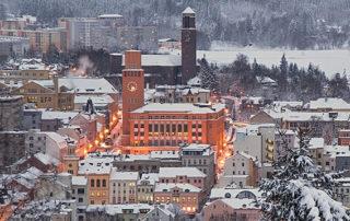 Zimní Jablonec nad Nisou večer – zasněžená rozsvícená radnice v pozadí s kostelem Nejsvětějšího Srdce Páně a přehradou