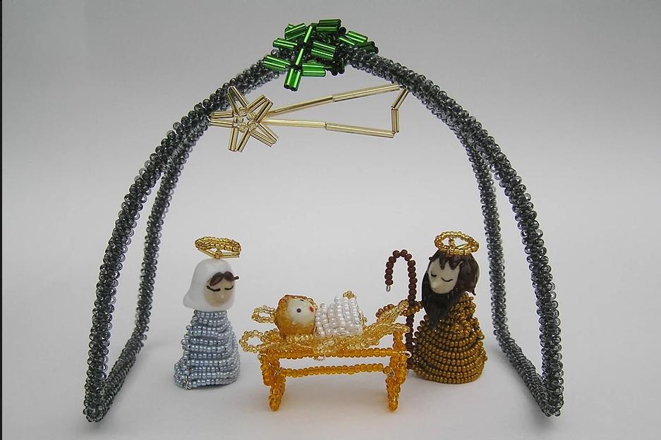 Jednoduchý betlém ze skla a korálků s postavami Ježíška, Marie a Josefa v Minimuzeu betlémů v Železném Brodě