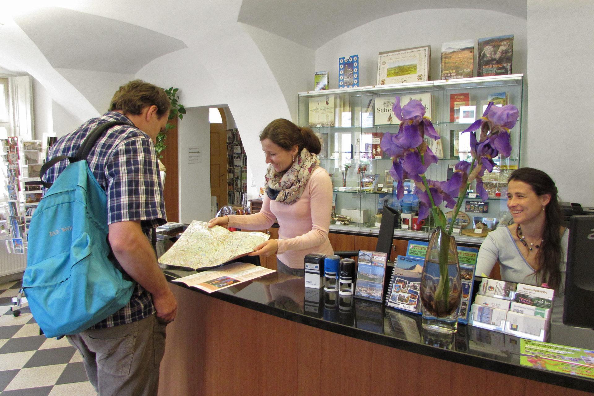 Pracovnice turistického infocentra v Jablonci nad Nisou obsluhují zákazníka a ukazují mu výletní cíle na mapě Jizerských hor.