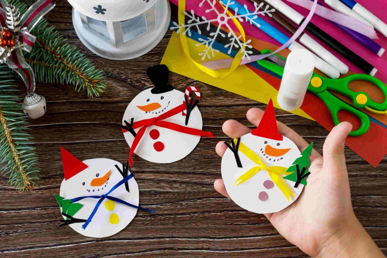 Dítě drží papírového sněhuláka veselý dárek. Ruční. Projekt dětské kreativity, řemesel, řemesel pro děti.