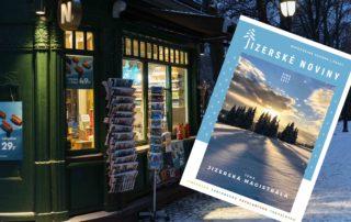 Turistické Jizerské noviny na zimu 2021 na pozadí svíticího kiosku v zasněženém parku
