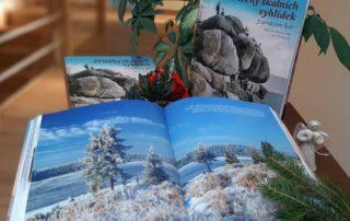 otevřená kniha Příběhy skalních vyhlídek Jizerských hor na pozadí jedné z vyhlídek se vánočními dekoracemi