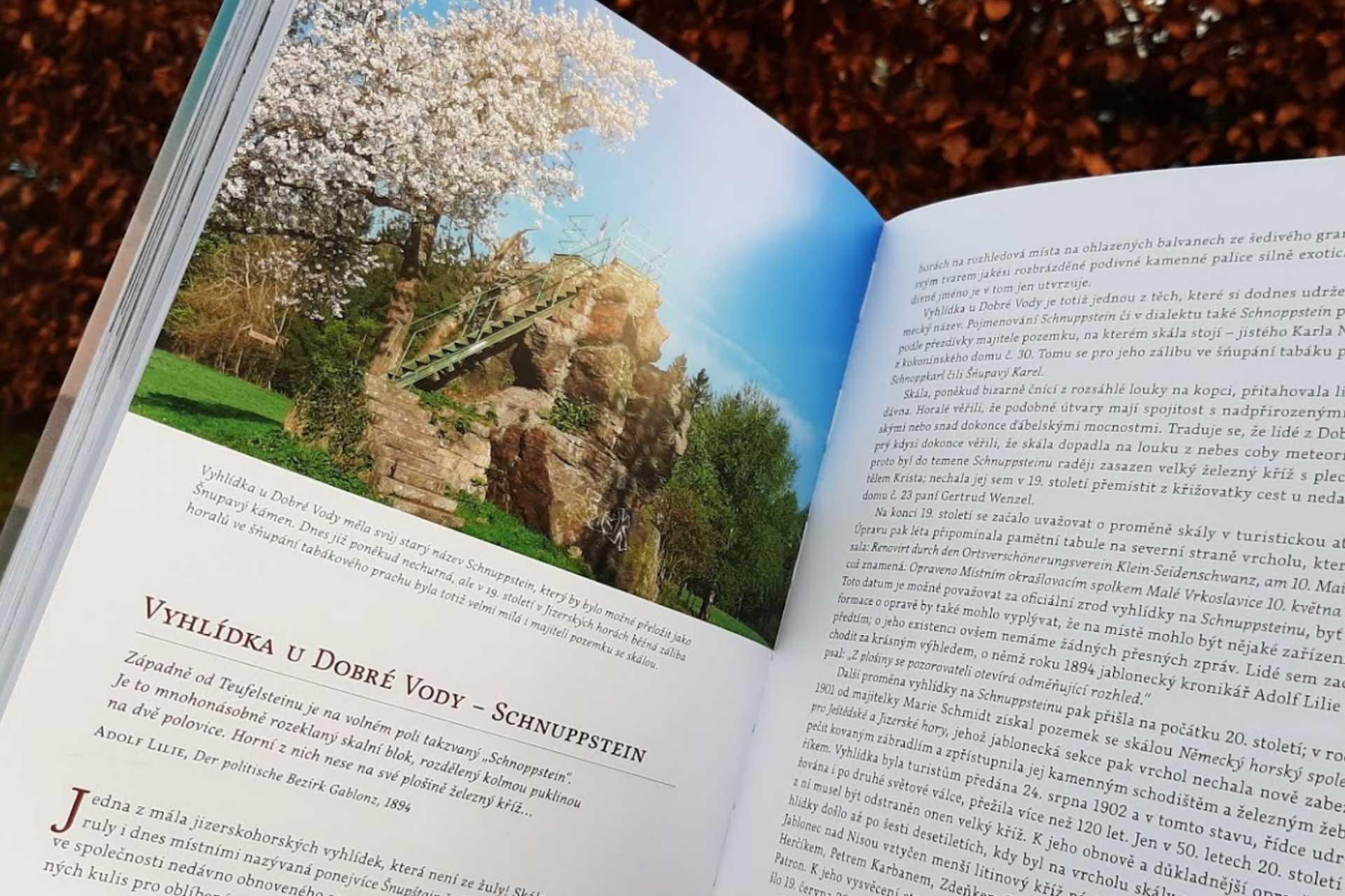 otevřená kniha Příběhy skalních vyhlídek Jizerských hor na pozadí jedné z vyhlídek na stránce o vyhlídce na Dobré Vodě v Jablonci nad Nisou