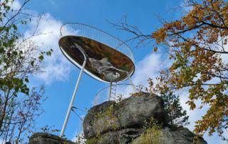 Originální lesklá kovová rozhledna Špička na vrcholové skále Malého Špičáku (Tanvald, Jizerské hory), která má svým tvarem připomínat skořepinu závodního bobu.