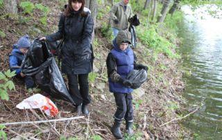 Žena, děti a starší muž uklízejí na jaře okolí jablonecké přehrady, sbírají odpadky do pytle - akce - Ukliďme Česko