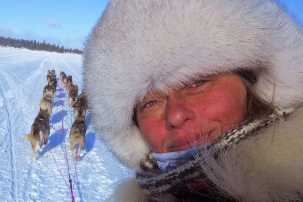 Musherka Jana Henychová v kožešinové čepici, vpozadí huski spřežení
