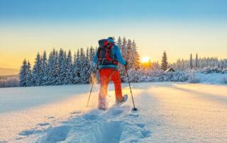 Muž jdoucí prašanem se sněžnicemi zimní krajinou s lesem a zapadajícím sluncem - Jizerské hory.