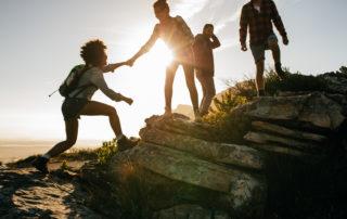 Trojice mladých lidí při západu slunce vylézá na skalku - turistika