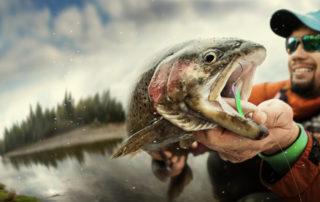 Mladý muž drží ulovenou rybu. Rybařit lze v Jablonci na přehradě.