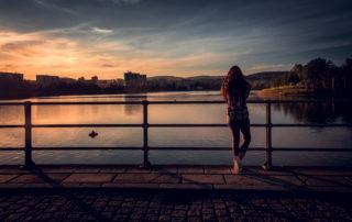 Dívka stojící při západu slunce na hrázi jablonecké přehrady Mšeno