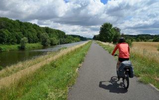 Cyklistka jedoucí podél řeky - mezinárodní cyklotrasa Odra-Nisa