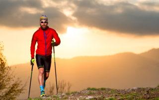 Sportovně vypadající muž s holemi nordic walking na procházce v horách při západu slunce