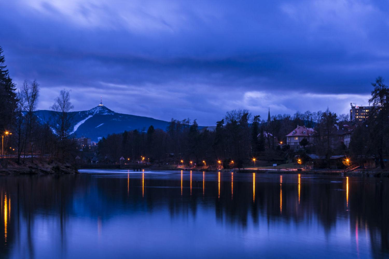Večer u přehrady harcov v Liberci - vodní plocha, osvětlrný břeh a Ještěd v pozadí