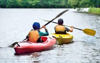 Dvě děti v kánoiích na přehradě