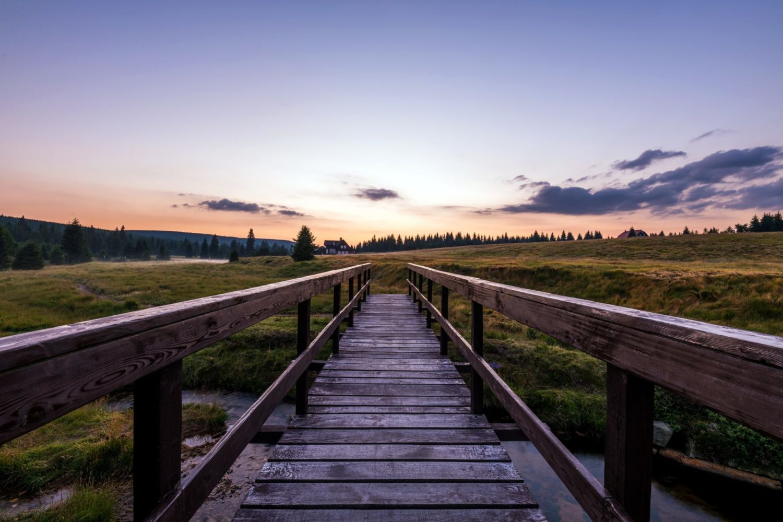 Dřevěný most přes rašeliniště v osadě Jizerka při východu slunce - Jizerské hory