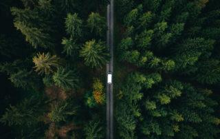 Pohled ze vzduchu na silnici protínající les a po ní jedoucí malý bílý autobus