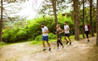 Skupina mladých lidí při kondičním běhu v lese