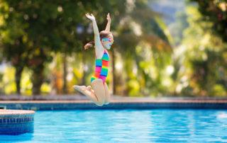 Dívka v plavkách skákající do vody na koupališti