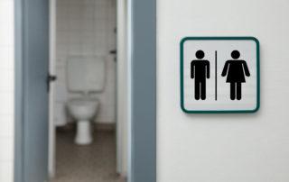 Otevřené dveře s průhledem na uklizené veřejné WC a označením pro dámské a pánské toalety