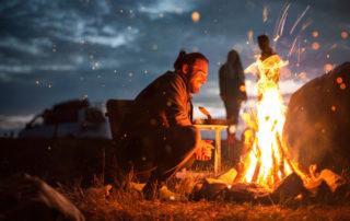 Usmívající se mladý muž sedící u ohniste ve tmě. Takový zážitek nabízejí v Jablonci i veřejná ohniště.