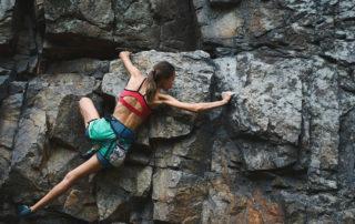 Sportovkyně lezoucí na skálu, ruce se pevně drží sklaních úchytů - outdoor life