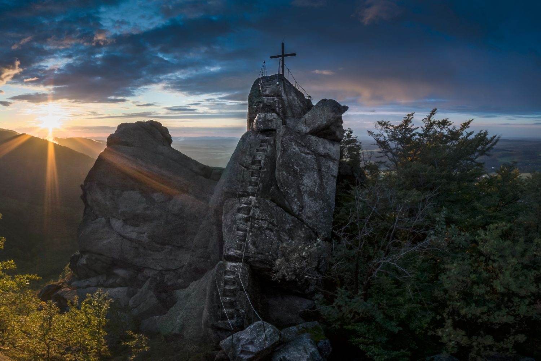 Západ slunce na vyhlídce Ořešník – skalní dominanta nad Hejnicemi, Jizerské hory. Pohled na skálu se strmými schody a křížem