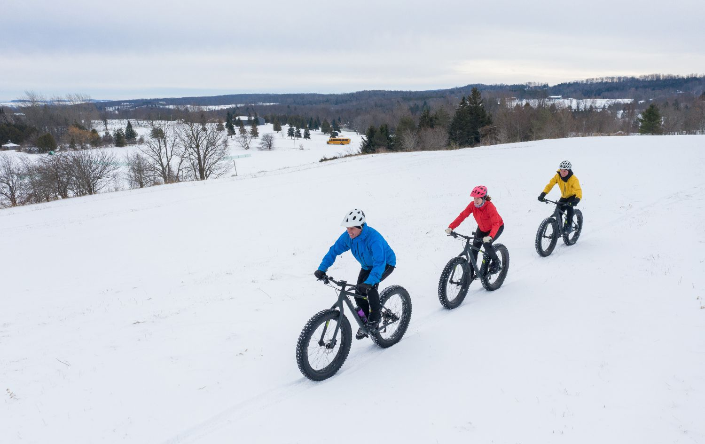 Tři cyklisté jedoucí zimní krajinou na speciálních kolech fatbike - Jizerské hory