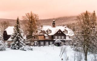 Zasněžená Šámalova chata na Nové Louce, dříve lovecký zámeček Clam-Gallasů, uprostřed lesů v Jizerských horách nabízí občertvení turistům i lyžařům.