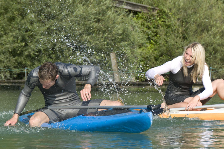 Dvojice mladých lidí cákající vodu a sedících na paddleboardu na přehradě v Jablonci nad Nisou