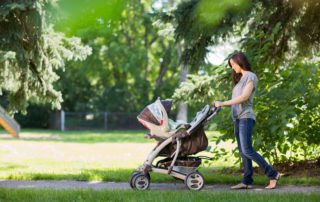 Mladá maminka tlačící kočárek v létě v parku - Jablonec nad Nisou