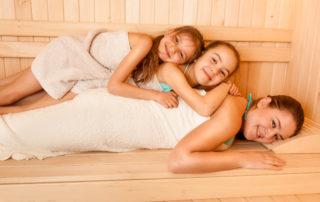Dvě malé dívky v ručnících ležící s matkou v sauně - sauny a relax jablonec nad Nisou