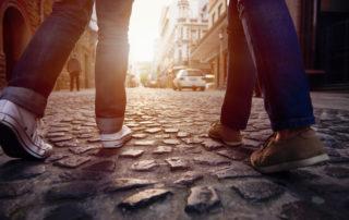 Pár turistů procházející se při západu slunce městem - záběr nohou na dlažbě. V Jablonci mohou pro lepší orientaci využít služeb průvodců.